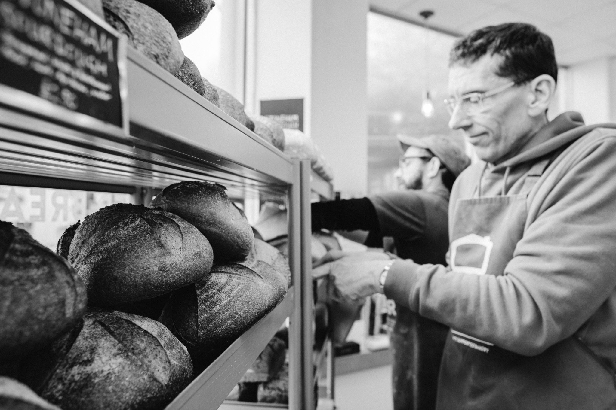 volunteer bakers stack the shelves with bread
